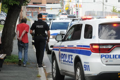 RNC officers are shown with an individual detained at the scene of an incident on Lemerchant Road in St. John's Saturday afternoon. The man had been searched and handcuffed, but had the handcuffs removed before being placed in the rear of a patrol car and taken from the scene. — Joe Gibbons/The Telegram