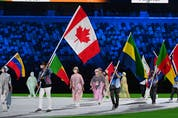 Canada's Damian Warner carries his national flag during the closing ceremony of the Tokyo 2020 Olympic Games, at the Olympic Stadium, in Tokyo, on August 8, 2021.