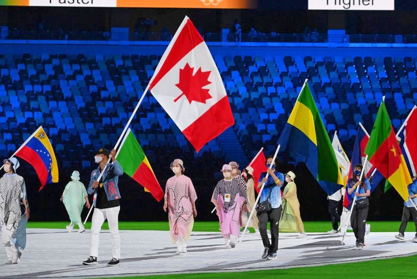 Canada's Damian Warner carries his national flag during the closing ceremony of the Tokyo 2020 Olympic Games, at the Olympic Stadium, in Tokyo, Aug. 8, 2021. - Postmedia  photo
