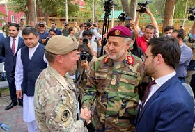 U.S. General Austin Miller, (left) shakes hand with Afghan Defense Minister Bismillah Khan Mohammadi on July 12, at a ceremony during the final phase of the withdrawal from the war in Afghanistan. Now Canada is scrambling to help Afghans who assisted its forces during the NATO-led effort. - REUTERS