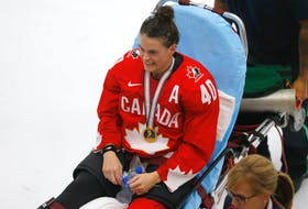 Blayre Turnbull of Stellarton rests on a stretcher with her gold medal following Canada's 3-2 overtime win over the United States in the championship game of the IIHF women's world hockey championship on Tuesday in Calgary. Turnbull suffered a broken fibula in the celebration of the victory. POSTMEDIA