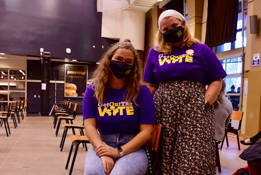 Samantha MacLean, left, and Sierrah Laybolt stand ready to help out at the Charlottetown candidates' debate at UPEI Sept. 8. Both are part of the UPEI student union, which helped organize the event.