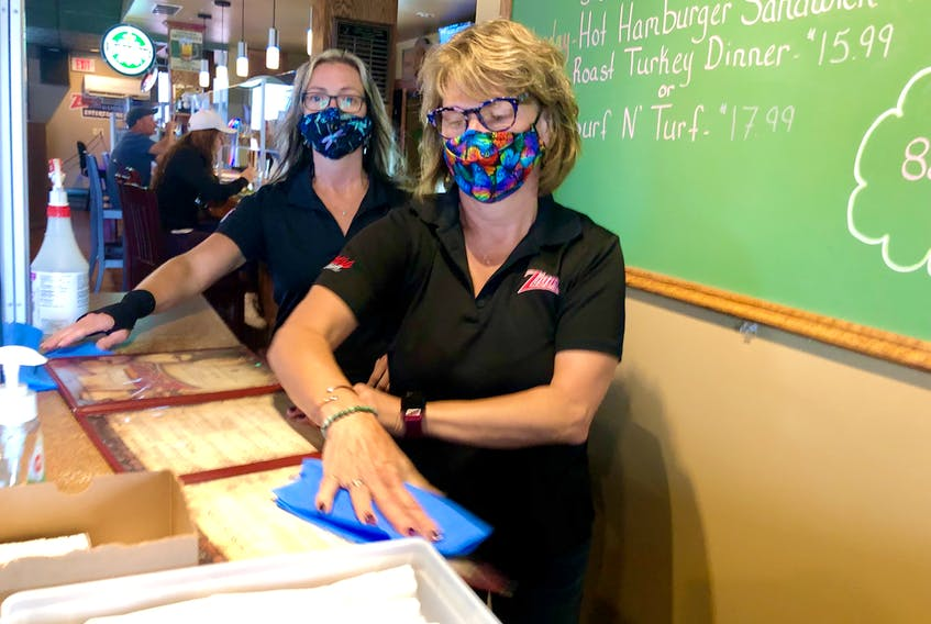 Ziggy's Pub and Grill servers Jenny Stone, front, and Karen MacKay stand in the station at the front of the restaurant where customers pay for their meals; which is now behind a Plexi-glass divider, a health protection measure put in place due to the COVID-19 pandemic. NICOLE SULLIVAN/CAPE BRETON POST