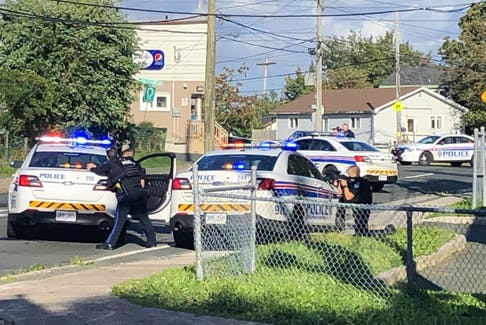 Police with drawn weapons aim at a residence on Campbell Ave. in St. John's Saturday afternoon. — Joe Gibbons/The Telegram