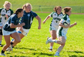 UPEI's Annika Wadlegger (right) breaks free from a pack of St. Francis Xavier tacklers as Panthers teammate Brinten Comeau (7) looks on during the AUS women's rugby season opener Saturday in Charlottetown. Wadlegger and Comeau had second-half tries in UPEI's stunning 38-31 victory over the X-Women. - Janessa Hogan / UPEI ATHLETICS