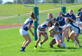 The UPEI Panthers' Kenzie Hale, holding the ball, attempts to escape the tackle attempts of the St. Francis Xavier X-Women. Maddy Clements, right, of the Panthers, supports Hale. The Panthers' won the Atlantic University Sport women's rugby game at UPEI 38-31 on Sept. 11.