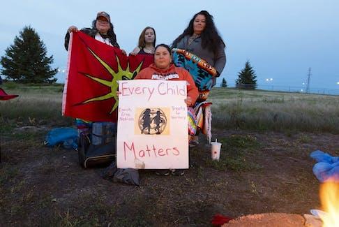 Lyndsay Breadner, left, Trinity Brandon-DeMeuse, Lorelei Mullings and Andrea Jenkins take part in an unmarked graves vigil for children of residential schools on Friday, Sept. 10, 2021 in Edmonton.