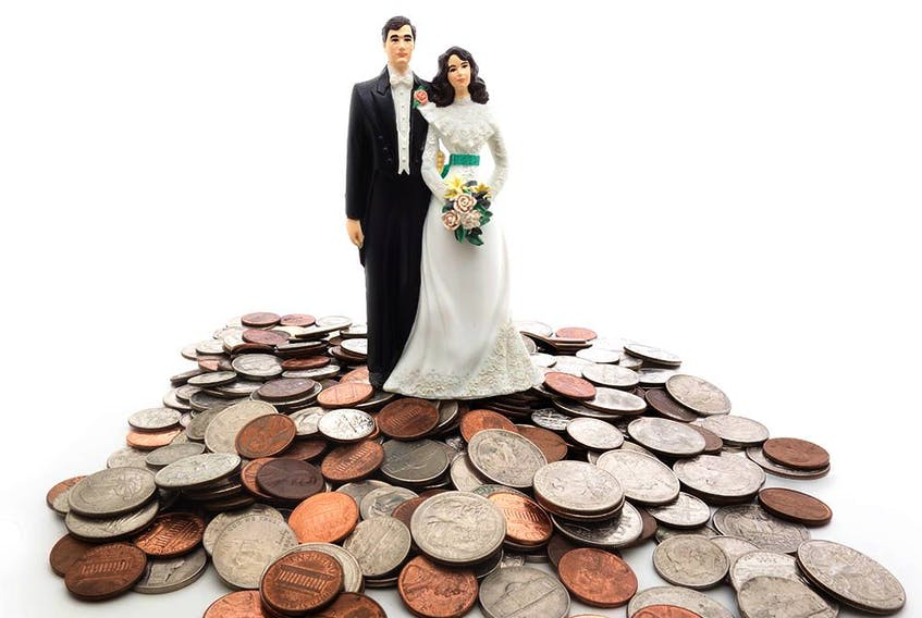 Plastic wedding couple on a pile of coins - money concept. Getty Images/iStockphoto