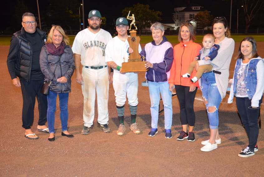 Valerie Grady, fifth from the left, presents the Colin (Coke) Grady Memorial championship trophy to Capital District Islanders co-captain Elijah Hood, fourth left, recently. The Island Junior 22-Under Baseball League (IJBL) named its championship trophy in memory of Grady, a respected player and minor baseball instructor in Summerside. Also taking part in the presentation are, from left, Blair Creelman, vice-president of the IJBL; Darlene Grady, daughter of Coke Grady; Johnny Savidant, co-captain of the Islanders; daughter Shelly Williams; Breanna Sheppard and Beau Palmer, granddaughter and great-grandson, and granddaughter Kayla Grady.
