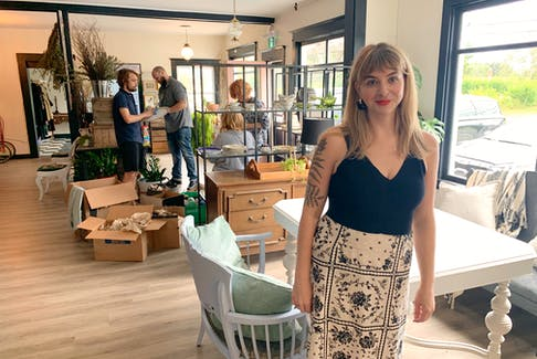 Morgan Giffin will open Rosa Rugosa, a market and restaurant in Hubbards, on Wednesday. In the background, workers stock the market's shelves in advance of opening.