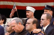 Members of the New York Fire Department embrace at the funeral of Father Mychal Judge, a fire department chaplain who died on duty on September 11, 2001 as the World Trade Center towers collapsed.