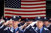 Members of the New York Fire Department salute to the casket of Father Mychal Judge, a fire department chaplain who died on duty on September 11, 2001 as the World Trade Center towers collapsed.