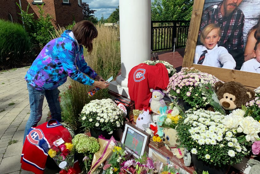 A woman places a card on a memorial to RJ Sears and Michelle Robertson and their four children in Amherst's Victoria Square. The family died in a fire in Millvale, Cumberland County on Sunday.