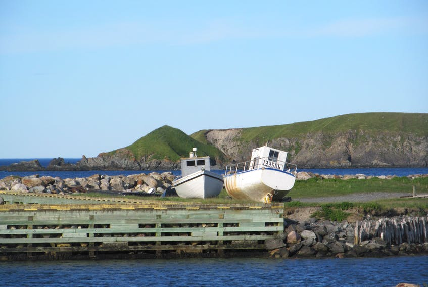This photo was taken by Jantje VanHouwelingen in Ferryland, N.L.  It really is a beautiful shot of coastal Newfoundland and Labrador with a pair of boats sitting up on the land and the rugged coastline of that part of Newfoundland in the background. It's an idyllic setting for a postcard, don't you think?