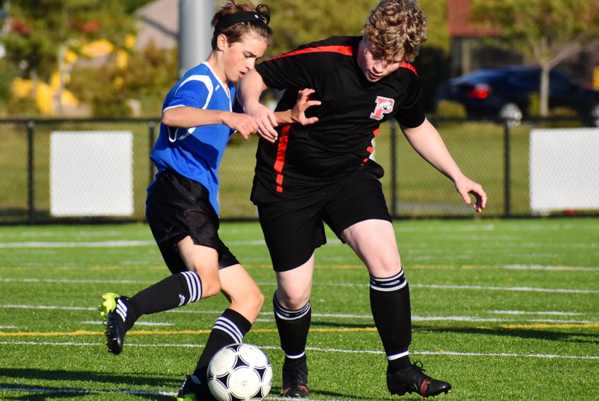 Cole Hutchison-Mills of the Sydney Academy Wildcats, left, works his way around Zack O'Keefe of the Glace Bay Panthers during opening day of the Cape Breton High School Soccer League boys action at Open Hearth Park Turf in Sydney on Monday. Sydney Academy won the game 4-1.  JEREMY FRASER/CAPE BRETON POST.