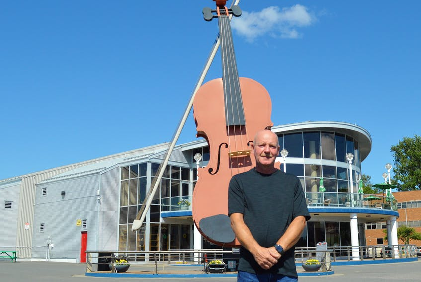 Dennis Hearn stands in front of the iconic Big Fiddle, a steel sculpture he and his brother Cyril Hearn built in 2004. Standing 17-metres tall and weighing eight tons, the steel sculpture is considered the largest fiddle in the world. Chris Connors/Cape Breton Post