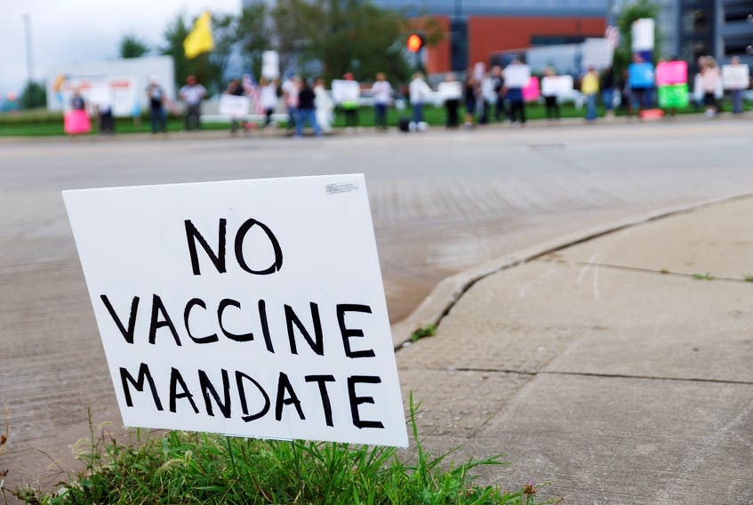 A sign against COVID-19 vaccine mandates is seen in the grass during a protest at Summa Health Hospital in Akron, Ohio. U.S. President Joe Biden recently urged unvaccinated Americans to get jabs and declared 'vaccine mandates' that oblige federal employees and companies that employ more than 100 people to do so. REUTERS/Stephen Zenner