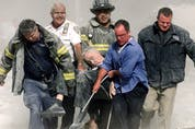 Rescue workers carry mortally injured New York City Fire Department chaplain, the Rev. Mychal Judge, from the wreckage of the World Trade Center in New York City on Sept. 11, 2001. His was the first recorded death on 9/11.
