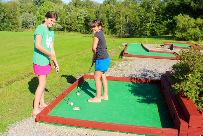 Maddie Maloney, 11, left, and Alex Maloney, 9, prepare to putt while playing mini-golf at the Red Barn Gift Shop and Restaurant in Nyanza, Victoria County, on Monday. The Sydney sisters were taking a road trip with their grandmother Phyllis Crocker and great-aunts Jenny Rideout and Gladys Everard, who were visiting from Newfoundland. Chris Connors • Cape Breton Post