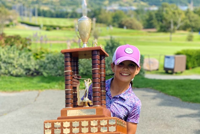 Freya Snook, 11, stands with the Baly Hally Junior Women's Championship trophy she won this summer.