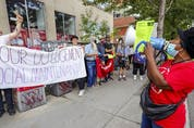 Housing activist Maryan Kikhounga-Ngot leads songs at a demonstration outside Liberal Leader Justin Trudeau's riding office in Montreal on Tuesday, Sept. 14, 2021.