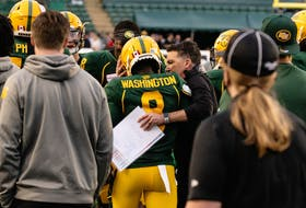 Edmonton Elks' Trumaine Washington (8) is congratulated by head coach and offensive co-ordinator Jaime Elizondo after an interception return for a touchdown against the Calgary Stampeders at Commonwealth Stadium in Edmonton on Saturday, Sept. 11, 2021.
