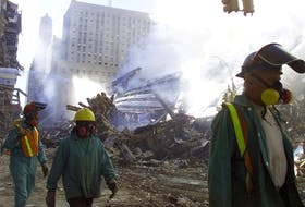 Rescue workers walk the dust lined streets of Manhattan as fires still burn from the World Trade Centre on Wednesday, September 12/2001.