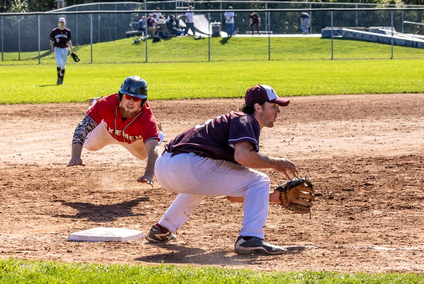 Kieran Finn of the Acadia Axemen flies through the air as he dives for third base during Atlantic Collegiate Baseball Association action against the Holland College Hurricanes in Charlottetown on Sept. 11. Hurricanes third baseman Ben MacDougall awaits the throw.  Darrell Theriault • Holland College