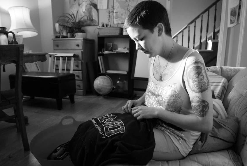 Delilah (Diem) Saunders died suddenly in Happy Valley-Goose Bay on Sept. 7. In this photo, Saunders is holding a sweater that belonged to their sister Loretta, who was murdered in Halifax in 2014. TANEA HYNES PHOTO