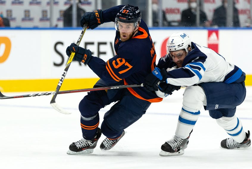 Edmonton Oilers captain Connor McDavid (97) battles Winnipeg Jets' Dylan DeMelo (2) during the first period of their NHL North Division playoff series at Rogers Place in Edmonton on Wednesday, May 19, 2021.