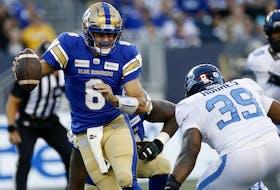 Winnipeg Blue Bombers quarterback Zach Collaros (8) scrambles away from Toronto Argonauts' Charleston Hughes (39) during the first half of CFL action in Winnipeg Friday, August 13, 2021.