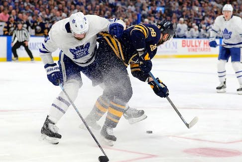 Toronto Maple Leafs defenceman Jake Muzzin checks Buffalo Sabres centre Zemgus Girgensons as he skates with the puck at KeyBank Center Feb. 16, 2020.