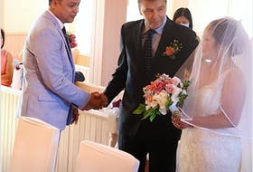 McDonald's employees Anapol (Apple) Camodoc, right, and her husband Denies Camodoc, left, both originally of the Philippines, during their wedding at St. Mary's Parish in Big Pond, with the franchise owner Wayne Kennerknecht by their side. A&R Images