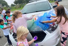 Many hands make great art, as youngsters attending a summer camp in Yarmouth gleefully realized while decorating an RCMP cruiser with officers' permission. CONTRIBUTED