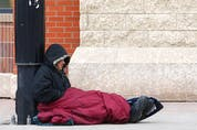 A homeless man tries to stay warm on the corner of 17th Avenue and 7th Street S.W. in downtown Calgary on Jan. 25, 2021.