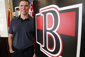 File photo/ The Belleville Senators' head coach, Troy Mann, stands next to the team's logo Tuesday, July 27, 2021 in Belleville.