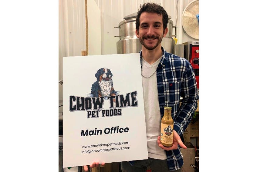 Chow Time Pet Foods CEO Zack Montreuil holds a bottle of his company's pet food sauce Kibble Drizzle.