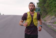 An exhausted Jodi Isenor descends French Mountain as he worked his way around the entire 300-kilometre Cabot Trail in one go. CONTRIBUTED