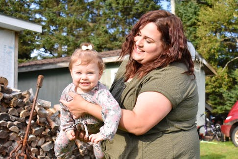 April Bernard swings her 19-month-old daughter, Tinsley, in the front yard of her father's Oyster Bed Bridge home.