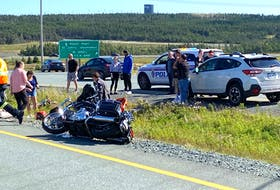 A motorcycle lies on its side at the shoulder of the highway, while just beyond, in the median, is a dirt bike at the site of a collision involving the two-wheel vehicles early Saturday afternoon on Peacekeepers Way. The crash occurred just west of the ramps providing connections the Trans Canada Highway on the outskirts of St. John's. — Keith Gosse/The Telegram