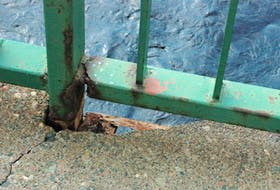 Rusted and deteriorating metal is exposed after a large piece of concrete has chipped away.