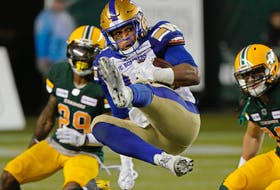 Winnipeg Blue Bombers running back Andrew Harris makes a leaping reception during a Canadian Football League game against the Edmonton Elks in Edmonton on Aug. 23, 2019.
