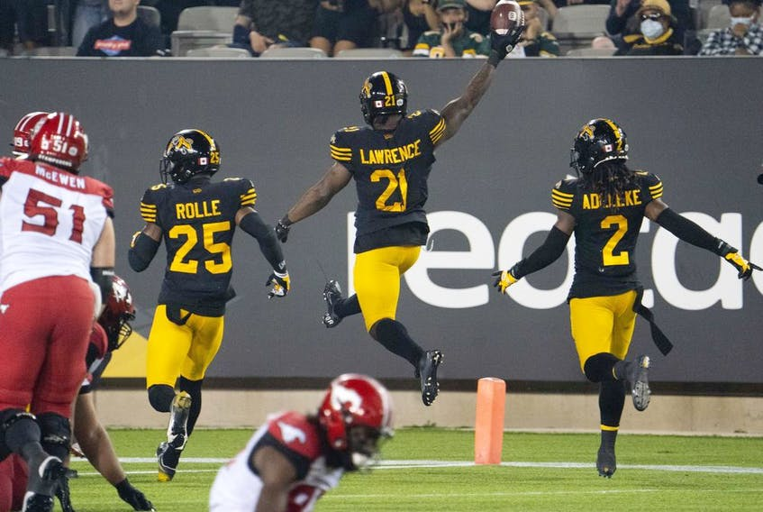 Hamilton Tiger-Cats linebacker Simoni Lawrence (21) celebrates his touchdown against the Calgary Stampeders at Tim Hortons Field in Hamilton, Ont. on Friday, Sept. 17, 2021.