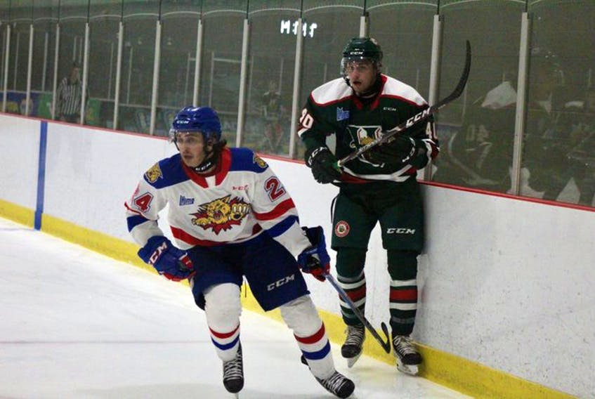 Halifax Mooseheads defenceman David Lafrance and Moncton Wildcats forward Ethan Dollemont track the puck during a QMJHL exhibition game in Moncton on Saturday.