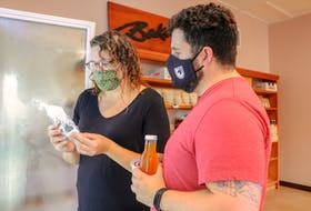 Katie MacLeod, left, and Joel Inglis, right, look at some product in one of the fridges at the Food Hub store on its opening day. JESSICA SMITH/CAPE BRETON POST