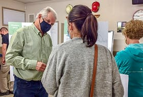 Community Wind Farms Inc. CEO Keith Towse, left, speaks to a community member at the Rhodena Wind open house in Port Hastings on Tuesday. CONTRIBUTED
