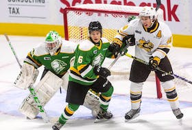 Sarnia Sting's Nolan DeGurse, right, battles London Knights' Denver Barkey in front of goalie Brett Brochu on Sept. 3 at Budweiser Gardens in London. The two teams were involved in a program called Hockey Fans in Training, in which 80 middle-aged men took part in discussions on healthy living and physical activity sessions.