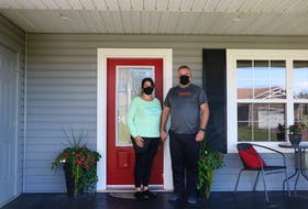 Serita Murphy, left, and her husband Kirk stand just outside the door of their home, in compliance with public health self-isolation measures. The two parents of a West Royalty student who tested positive for COVID-19 say they want a vaccine mandate for teachers and school staff implemented immediately. Stu Neatby • The Guardian