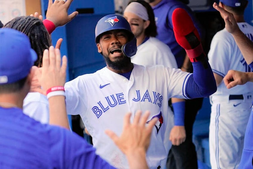 Blue Jays right fielder Teoscar Hernandez (centre) celebrates scoring during the first inning against the Minnesota Twins at Rogers Centre on Sunday.