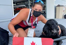 Canadian Paralympian Victoria Nolan with her guide dog, Alan, in front of the rowing course with one of the Canadian team's oars. Despite laws guaranteeing her and her dog access to shops and services in Canada, she says she is often denied that right.